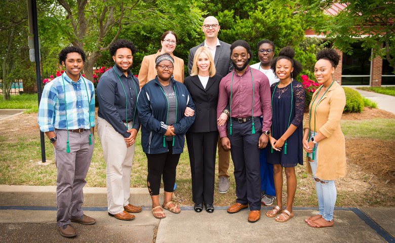 Renvy Pittman (center) enjoys spending time with the Grove Scholars whenever she visits campus. Here, she's pictured with alumni of the program — the 2018 seniors (from left) Jontae Warren, Devante Yates, Jessica Cole, Rashad Collier, Deshauntra Green, Bre O'Neal and Myrical Taylor. In back are Maura Scully Murry, director of the FASTrack Learning Community, and E. Gray Flora IV, director of Grove Scholars and senior academic mentor for FASTrack.